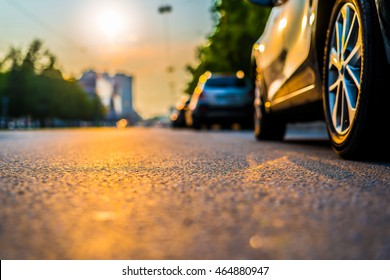 Sunset in the city, the cars traveling on the road. Close up view from the level of a parked car wheels