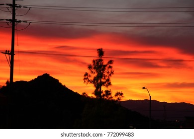 Sunset in a city with mountains in the background.