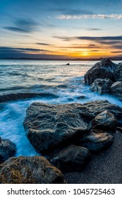 Sunset closes the day over the huge boulders at Polerris Beach in Cornwall. The view across the bay takes you to Spit Beach, Crinnis, Charlestown and Mevagissey.