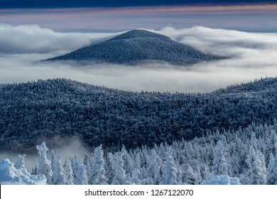 Sunset cloud inversions around winter mountains in Vermont.