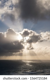 A sunset cloud over the sea which appears to be a skull, bear face or taniwha as seen from Anawhata Beach of Auckland, New Zealand. Sun rays shine upwards from the eyes and downwards from the mouth.