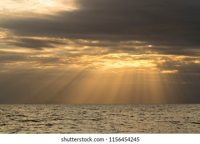 in sunset, cloudly weather, light rays appear between clouds