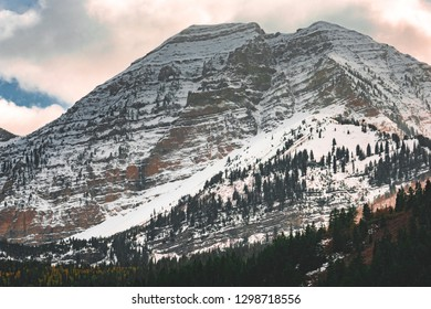 Sunset clouds and flurries of snow close out an autumn day on the peaks of Mount Timpanogos in American Fork Canyon in the Wasatch Mountain Range, Utah, United States.