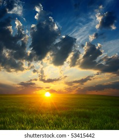 Sunset with clouds over field with green grass