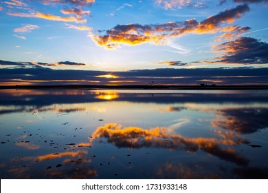 Sunset and clouds reflected in the mirror smooth waters of Lake Tyrrell, a salt lake near Sea Lake in North-West Victoria, Australia. A popular tourist destination.