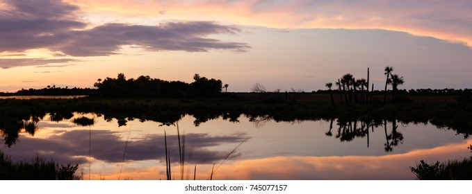 Sunset with clouds reflecting in a pond at Merritt Island National Wildlife Refuge, Florida, USA