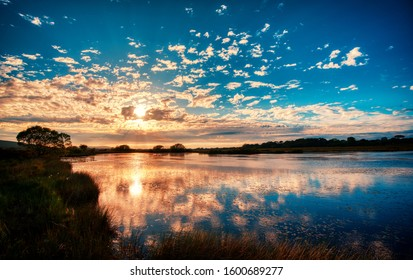 Sunset clouds and reflections off the surface of broad pool on the Gower peninsular