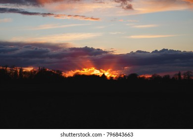 A sunset with clouds with a silhouette of trees
