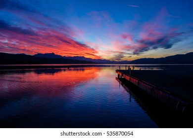 Sunset colored clouds over lake with a pier on the right side and sunset reflection in the water. Captured on Woerthersee, Kaernten, Austria.