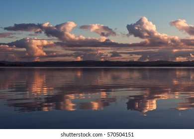 Sunset colored stormy clouds mirrored in the still water of a lake in western Oregon