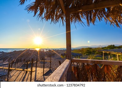 Sunset with colorful sun rays on the shore of the Adriatic Sea, paths sunbeds and umbrellas made of wood and straw in the recreation area on the sand. Beach on Ada Bojana, Ulcinj, Montenegro.
