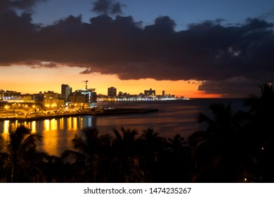 Sunset with colorfull sky and night view over the famous Malecon esplanade and skyline in Havana, capital city of Cuba.
