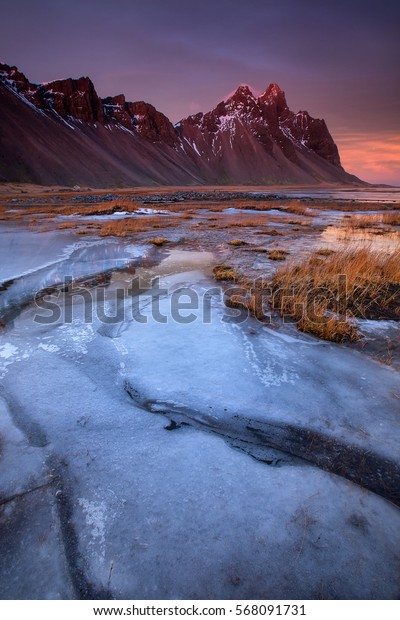 Sunset colors on winter ice at the Vestrahorn mountain on the Stokksnes Peninsula, Hofn, Iceland