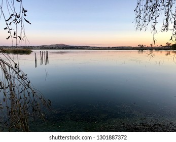sunset colours are reflected in the still waters of a calm lake. Willow leaves on branches can be seen in the foreground and the wood posts from an old jetty are visible in the distance.