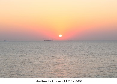 Sunset with container ships waiting on their turn to cross through Gallipoli seen from the island Bozcaada in Turkey.