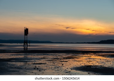 Sunset at Coos Bay Oregon Empire dock. Silhouetted wood pilings, industrial fishing wharf.