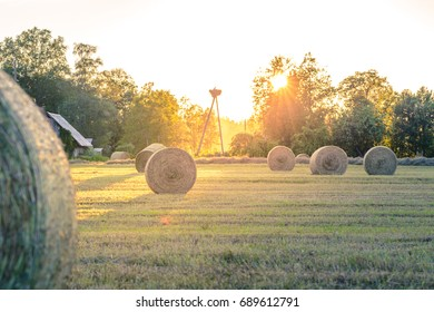 Sunset in countryside at mid summer. Hay rolls and road in misty weather with clear sunny sky. Beautiful nature in Latvia in August.