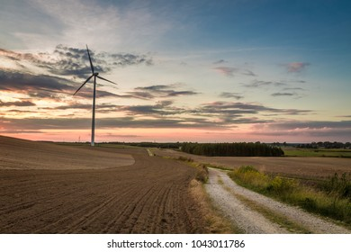 Sunset at countryside with wind turbine in Poland