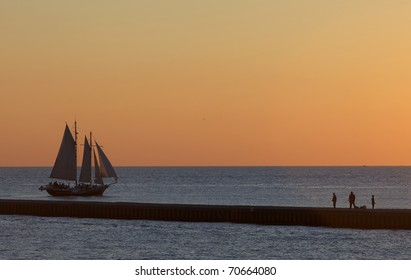 Sunset cruise aboard four sail large ship with the pier and fishermen in the fore ground. Lake Michigan is the setting for this sunset.