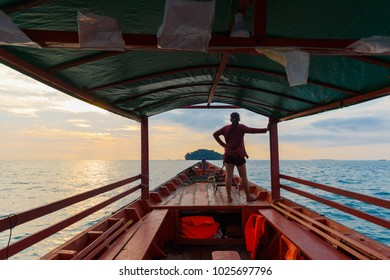 Sunset Cruise in Cambodia from Otres Beach with local woman standing on boat watching sunset