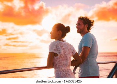Sunset cruise romantic couple watching view from boat deck on travel vacation. Silhouette of man and woman tourists relaxing on outdoor balcony of ship.