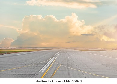 Sunset and cumulus clouds on the road runway in the airport