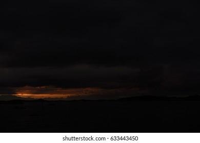 Sunset, dark sky with sunlight hole.
