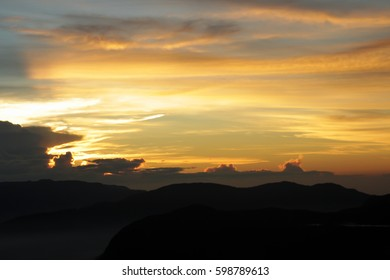 Sunset (dawn) in the mountains, the sun behind the clouds, the colorful sky