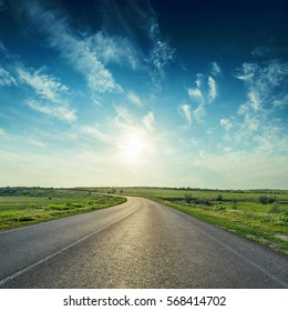 sunset in deep blue sky over asphalt road