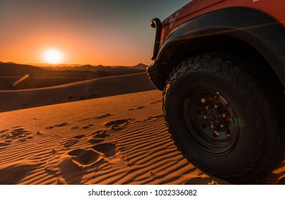 Sunset in the desert with details of a 4x4 vehicle