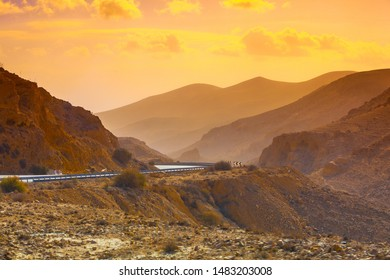 Sunset in desert. Driving a car on mountain road in desert. View of sandstone mountains through windscreen. Israel