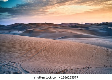 Sunset in the desert of Huacachina Ica, Peru. Dunes with marked car tracks