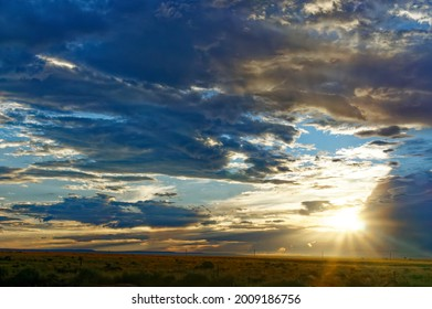 Sunset in the desert. A low sun frame right with dramatic clouds.