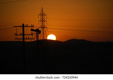 Sunset in the desert on the background of power lines