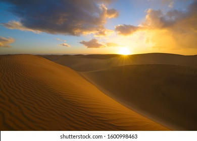 Sunset in the desert, sun and sun rays, blue sky and Beautiful clouds. Golden sand dunes in desert in Maspalomas, Gran Canaria at Canary islands, Spain