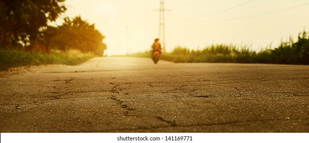 Sunset desserted highway with biker silhouette