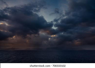Sunset and dramatic set of clouds drifting over the tropical waters of the Caribbean Sea are lit by the last moments of daylight.