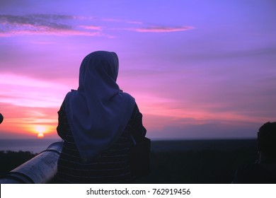 Sunset and dramatic sky with silhouette of muslim woman.