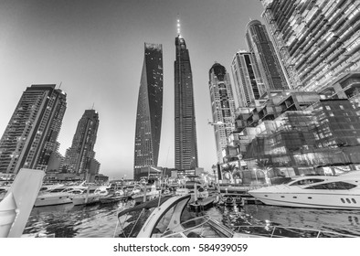 Sunset in Dubai Marina. Buildings reflections over artificial canal.