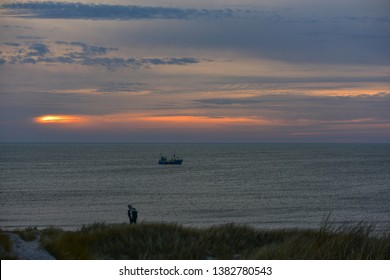 Sunset with dunes, young man and fishing boat at the North Sea near Soendervig/Western Denmark