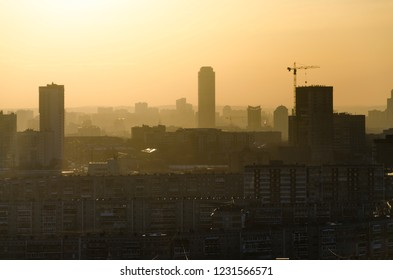 Sunset in Ekaterinburg. Golden mist in air, pollution and smoke in industrial city concept.