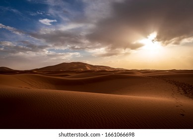 Sunset in the Erg Chebbi desert, Morocco. Is part of the Sahara. The sunset is near, the sun on the horizon. There are footsteps on the dunes, from the passage of caravans of dromedaries.