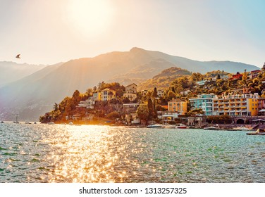 Sunset in the evening in Ascona luxury tourist resort promenade on Lake Maggiore in Ticino canton in Switzerland in summer. People outdoor street travel. Romantic Swiss typical expensive town.
