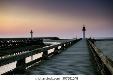 Sunset and Evening Mood at the Beach of Deauville with Pier and Lighthouse during Ebb Tide