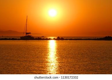 Sunset from famous beach of Vouliagmeni near Glyfada, Athens riviera, Attica, Greece