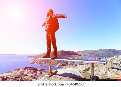 Sunset felling blur focus. Happy hiker backpack with hands in the air stand on chair top of rock . View over colour town evening valley by sunset background.qaqortoq greenland.