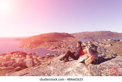 Sunset felling blur focus. Happy hiker backpack sit beside rock . View over co lour town evening valley by sunset background.qaqortoq greenland.