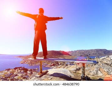 Sunset felling. Happy hiker backpack with hands in the air stand on chair top of rock . View over co lour town evening valley by sunset background.qaqortoq greenland.