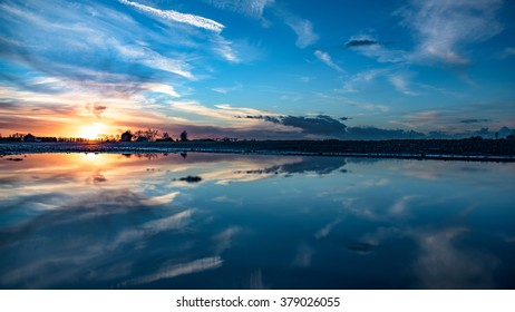 Sunset flat panorama landscape with blue sky and clouds reflected in water in 16x9 format without people and with copy space.