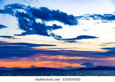 Sunset in Follonica viewing the Elba Island in late winter with cloudscape and shades of red